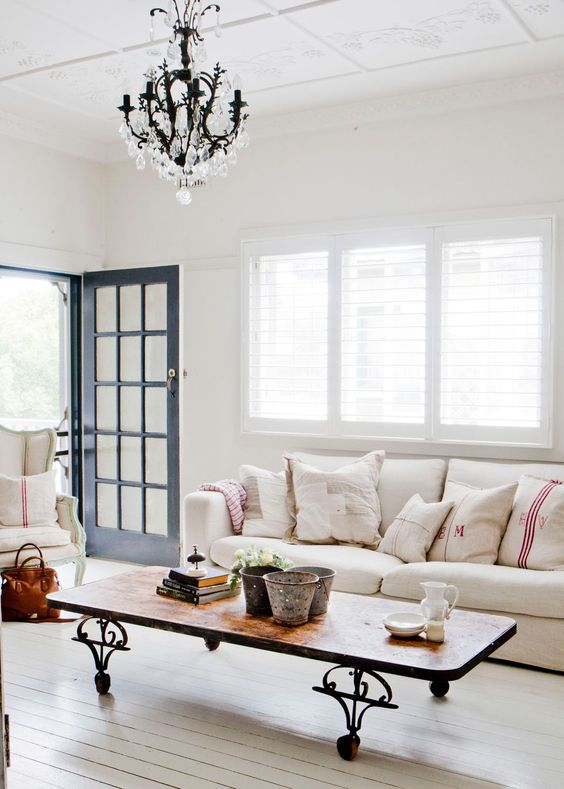 a French chic living room in neutrals, with a coffee table on casters, a crystal chandelier and striped pillows