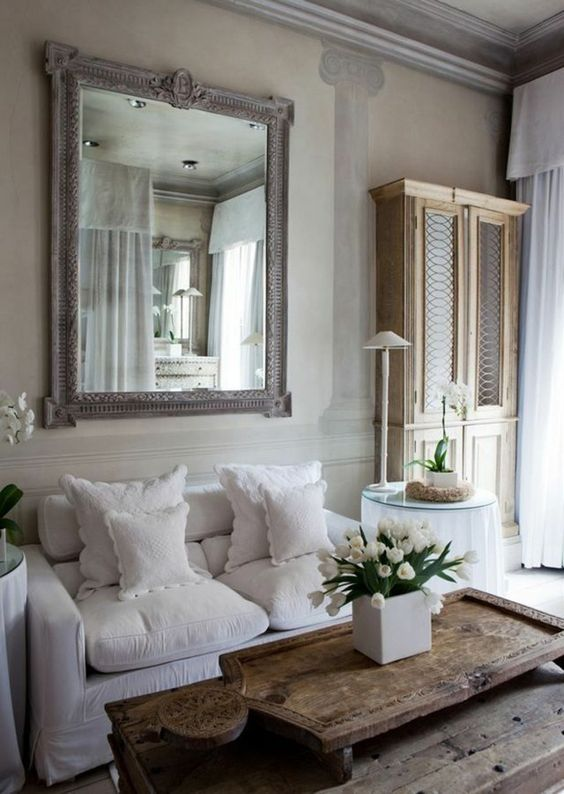 a Provence living room in neutrals, with a statement mirror, neutral furniture and a low wooden table plus mini round tables