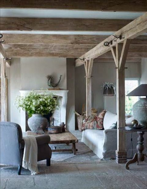 a Provence living room with wooden beams and pillars, with a fireplace and a white sofa plus a blue chair and cool lamps