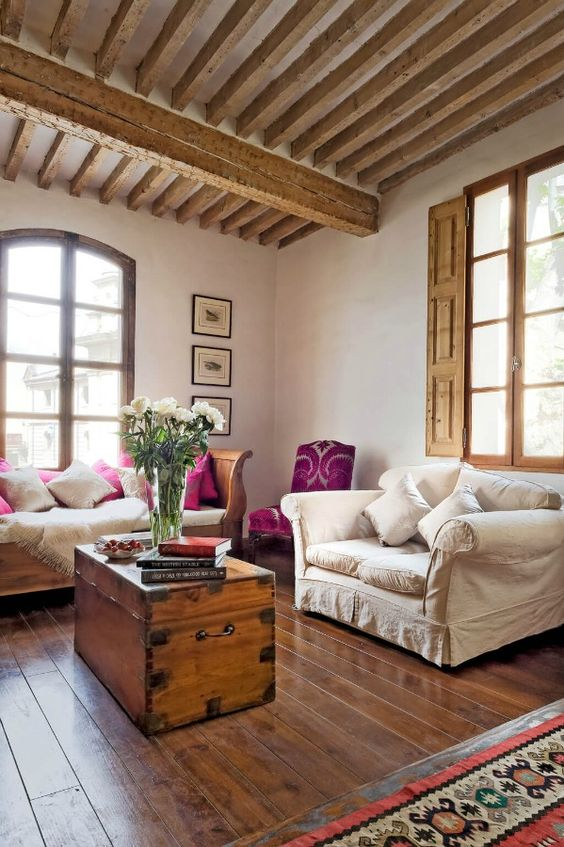 a Provence living room with wooden beams and shutters, neutral refined furniture, a chest in the center and a gallery wall