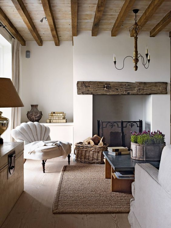 a beautiful Provence living room done in neutrals, with a wooden mantel over the fireplace and wooden beams, neutral furniture, a love table and a cool chandelier