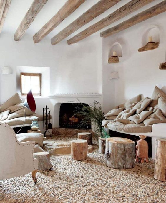a beautiful Provence living room with neutral furniture, a fireplace, wooden beams on the ceiling and a quirky stone floor