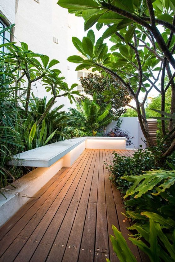a beautiful minimalist deck with a built-in bench, potted greenery, trees and plants, with built-in lights is amazing