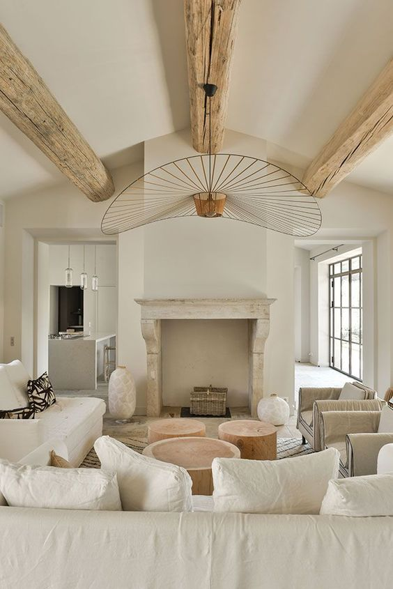 a beautiful neutral living room with wooden beams, a fireplace, neutral furniture, tree stumps as coffee tables