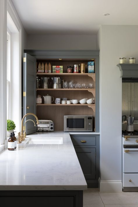a cabinet with appliances, jars, mugs, cups and other stuff is a little coffee station that can be hidden with a folding door