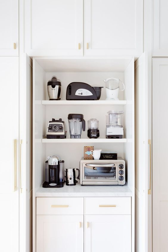 a cabinet with shelves holding various appliances is a cool and stylish idea to store them without cluttering the space