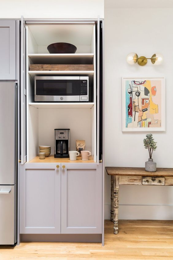 a cabinet with shelves that hides several appliances and creates a mini tea and coffee station you may use