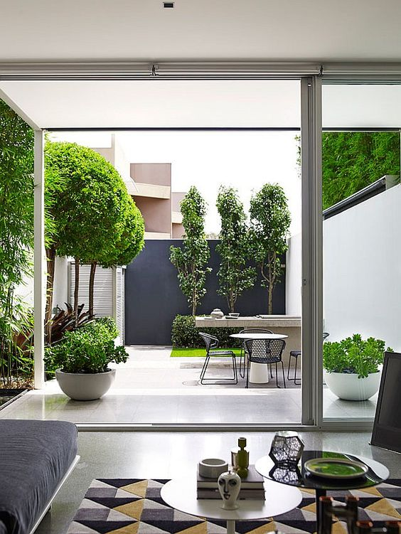 a catchy minimalist outdoor space with growing trees, grass and greenery, a stone table and metal chairs and a black accent wall