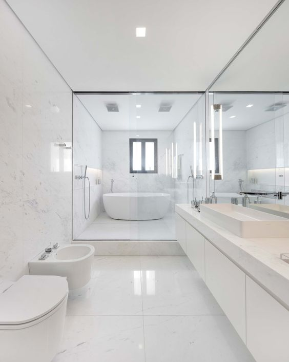 a chic minimalist bathroom clad with large scale white marble tiles, a floating marble vanity and white appliances