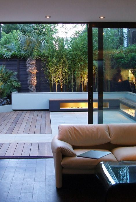 a chic minimalist terrace clad with wood and tiles, built-in lights in benches, growing trees is a stylish and cool nook to be in
