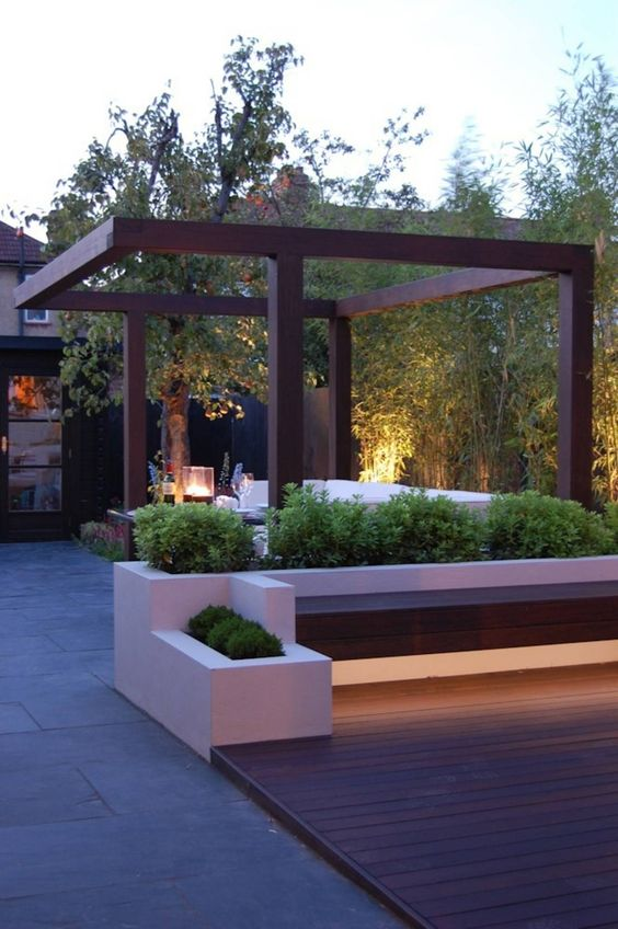 a chic minimalist terrace with a wooden deck, built-in benches and potted greenery, some lanterns is a lovely space to spend some time