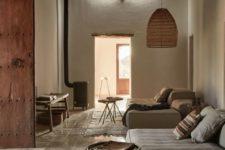 a chic wabi-sabi interior with white walls, a pendant lamp, a tile floor and a hearth