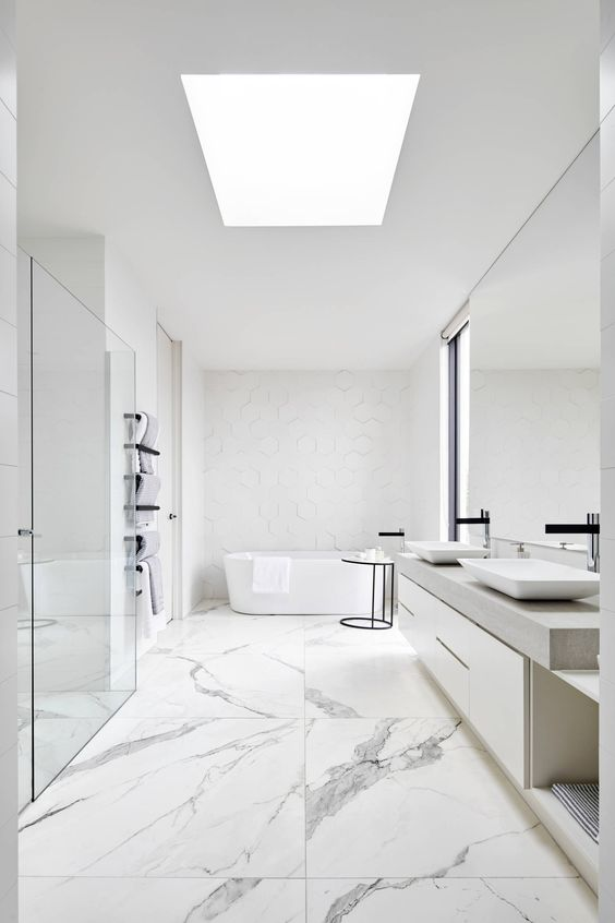 a chic white minimalist bathroom with marble large scale tiles, white furniture, white appliances and white hex tiles