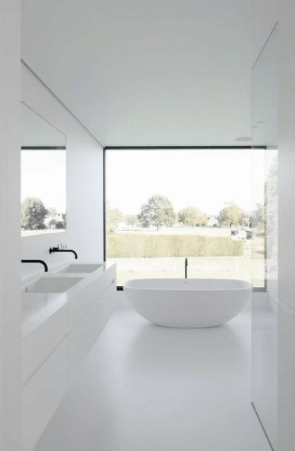 a clean all-white minimalist bathroom with a glazed wall, a white floating vanity, white appliances and black fixtures