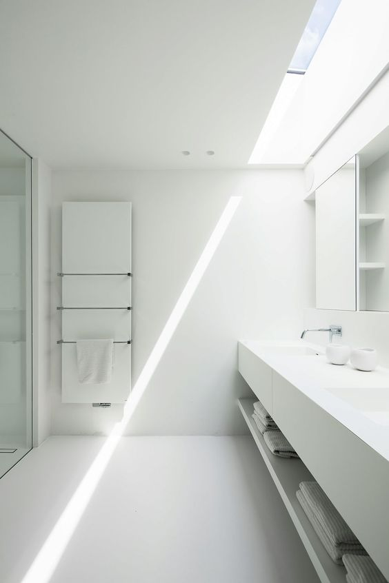 a clean white minimalist bathroom with a skylight, a floating vanity, a statement mirror cabinet and stainless steel fixtures