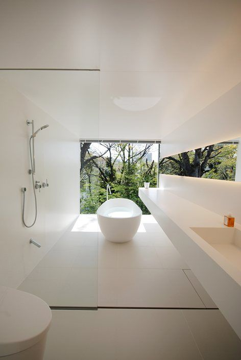 a concrete creamy bathroom with large scale tiles, a long floating vanity and a glazed wall for rainforest views