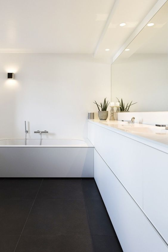 a contrasting black and white bathroom with a black tiled floor, a white long vanity, a bathtub clad in white and some built-in lights