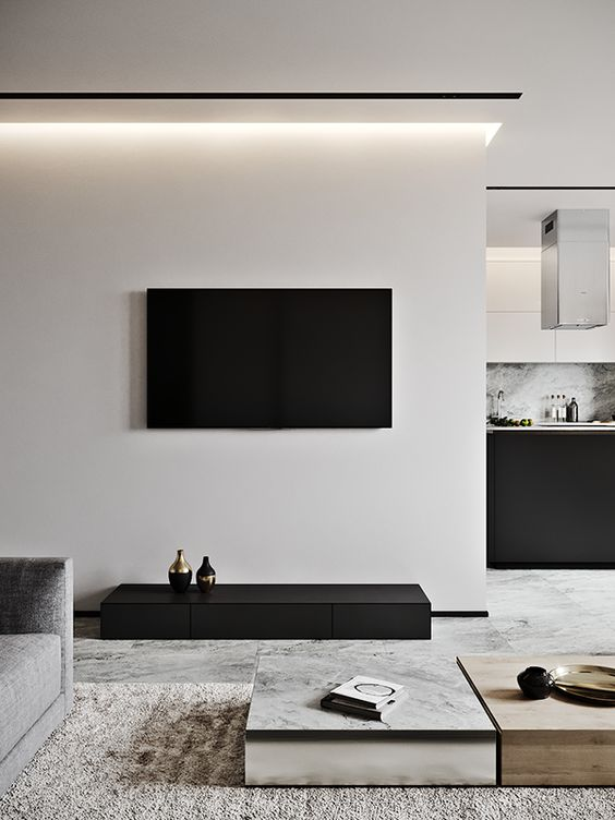 a contrasting living room in off-white and black, laconic coffee tables, a textural rug and built-in lights