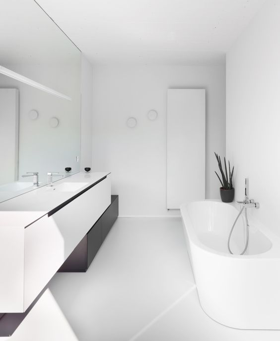 a contrasting minimalist bathroom with a floating vanity, a mirror wall, white appliances and built-in lights