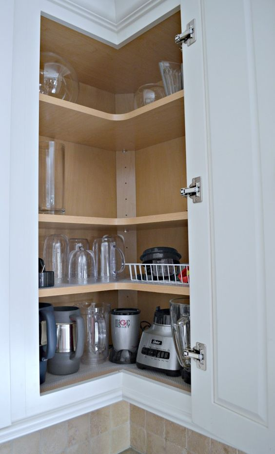 a corner cabinet with shelves that holds appliances and various mugs and glasses is a cool solution to save some space
