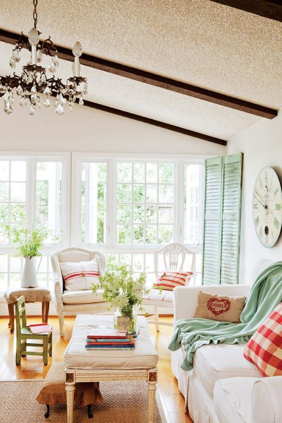 a cottage Provence with green shutters, neutral furniture, plaid and green textiles, a crystal chandelier and a jute rug