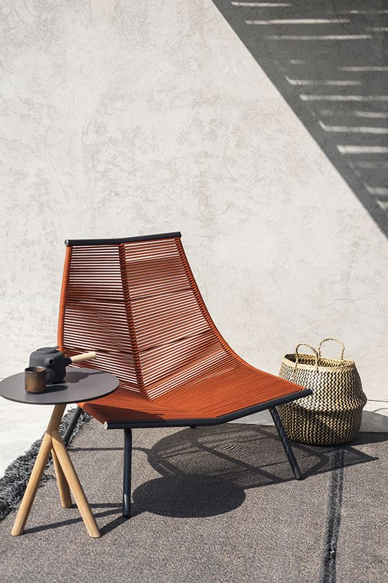 a creative lounger of a metal frame and some wicker in a rich brown shade looks really wow and really statement-like