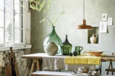 a dining space with wabi-sabi aesthetics, a wooden dining set, concrete wlals and a rough wooden floor plus vases