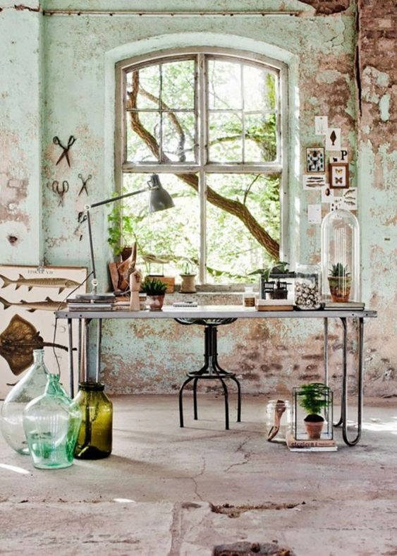 a farmhouse wabi-sabi home office with large bottles and vases, metal chairs and potted greenery and succulents