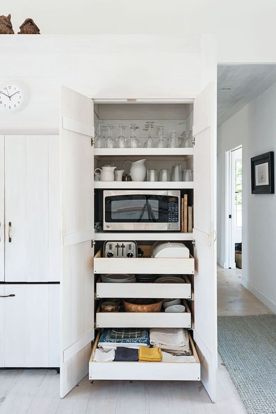 a functional cabinet with shelves and mini drawers holding glasses, mugs, cups and some appliances is a very smart idea