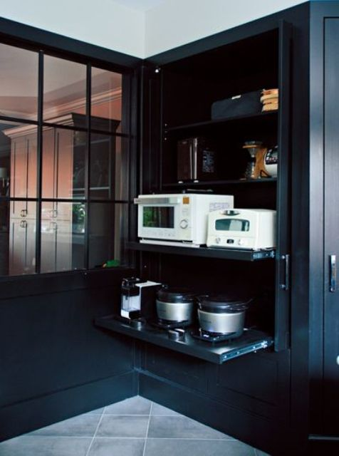 a large black cabinet holding all the appliances on retractable shelves helps to keep the kitchen in order and make it cooler
