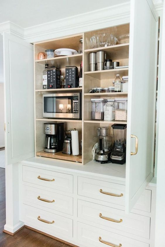 a large cabinet with all kinds of appliances, some bowls and jars is a cool idea to store what you don't need and hide it