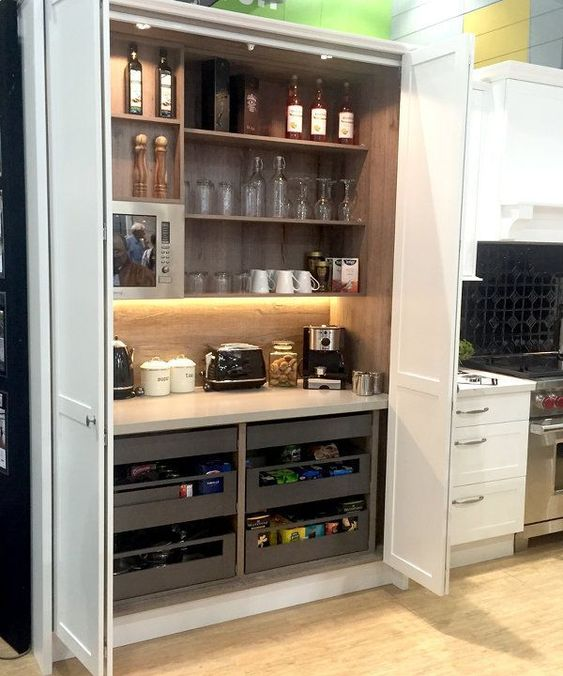 a large storage unit with open shelves and drawers, appliances, mugs, glasses, wine and other stuff is a good space for cooking here
