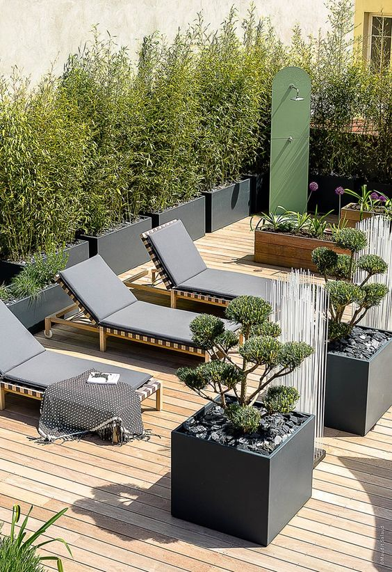 a lovely minimalist terrace with a wooden deck, black loungers, potted plants and blooms and a mini garden shower is cool