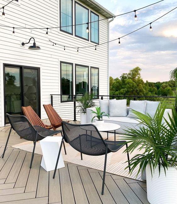 a lovely minimalist terrace with chevron wooden floors, a white low sofa, metal and wooden chairs, a sculptural side table and potted plants