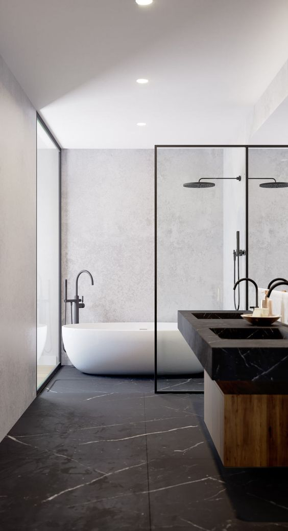 a luxurious minimalist bathroom with a black marble floor and sinks, a wooden vanity and black fixtures that echo with the marble