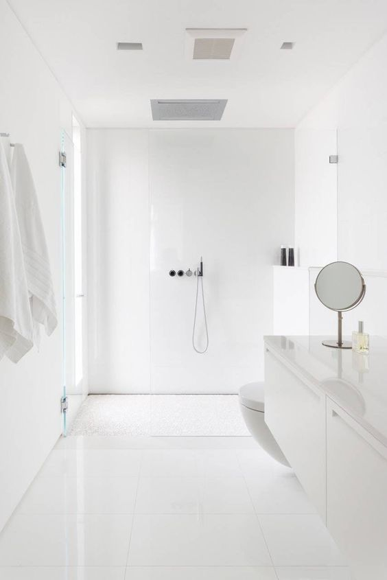 a minimal white bathroom clad with large scale tiles, a floating vanity, a a frosted glass window, some mirrors