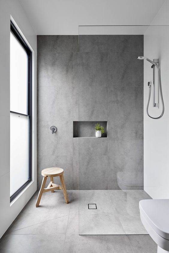 a minimalist bathing space with grey tiles, a frosted glass window, white appliances and a nice for storage
