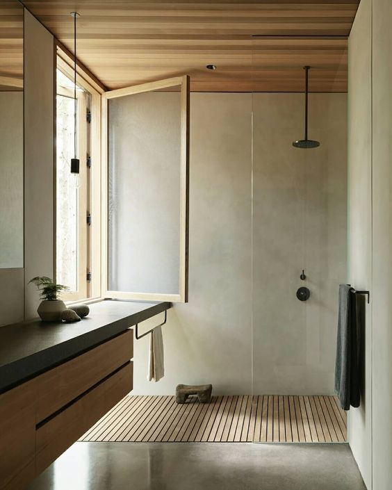 a minimalist bathroom clad with concrete, a flaoting wood and concrete vanity, a window and a wooden floor and ceiling