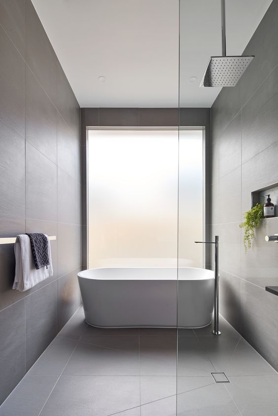 a minimalist bathroom clad with grey large scale tiles, a frosted glass window and some greenery