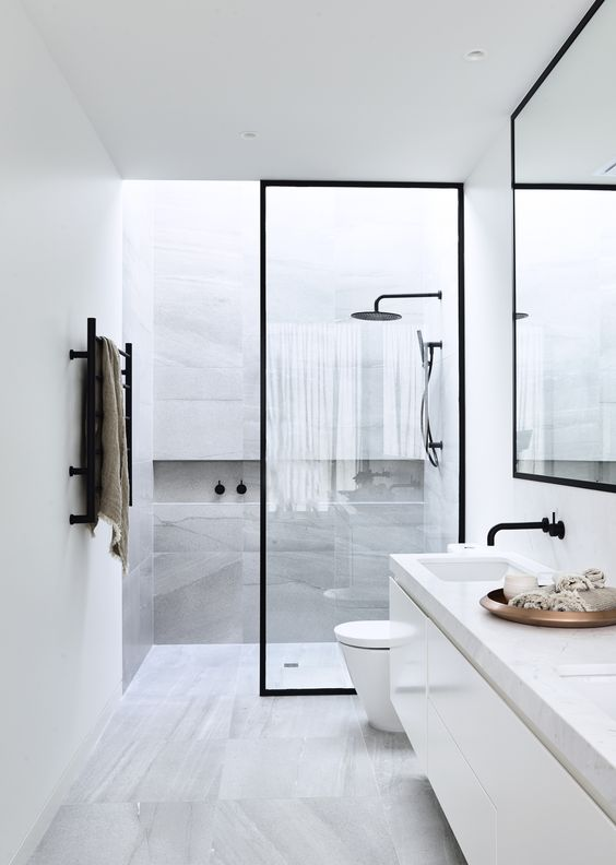 a minimalist bathroom clad with grey stone-like tiles, a floating vanity with a stone countertop, a shower with a skylight