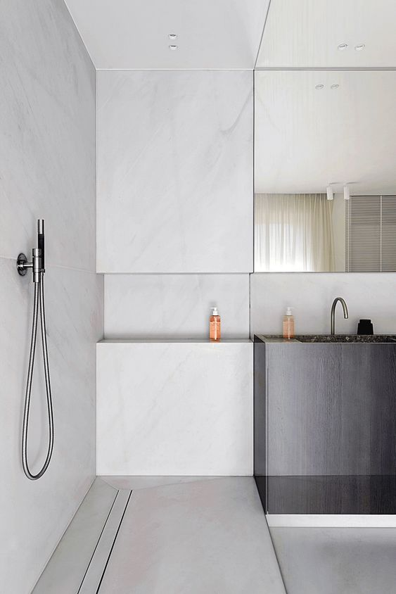 a minimalist bathroom clad with white marble, a dark vanity with a built-in sink and a statement mirror coming up the ceiling