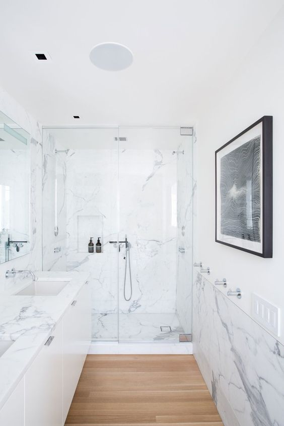 a minimalist bathroom clad with white marble, with a large floating vanity, a statement artwork