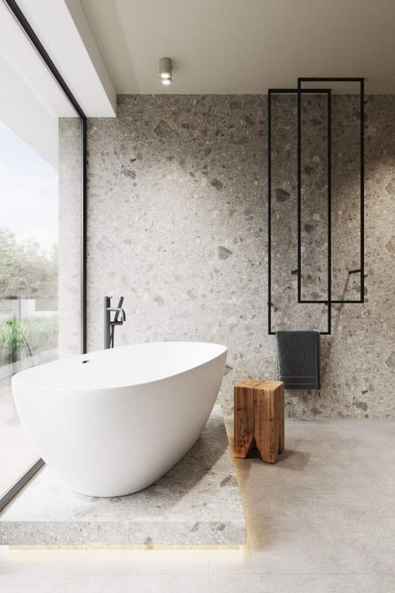 a minimalist bathroom with a glass wall, a bathtub on a stone platform, a stone wall and cool towel hangers