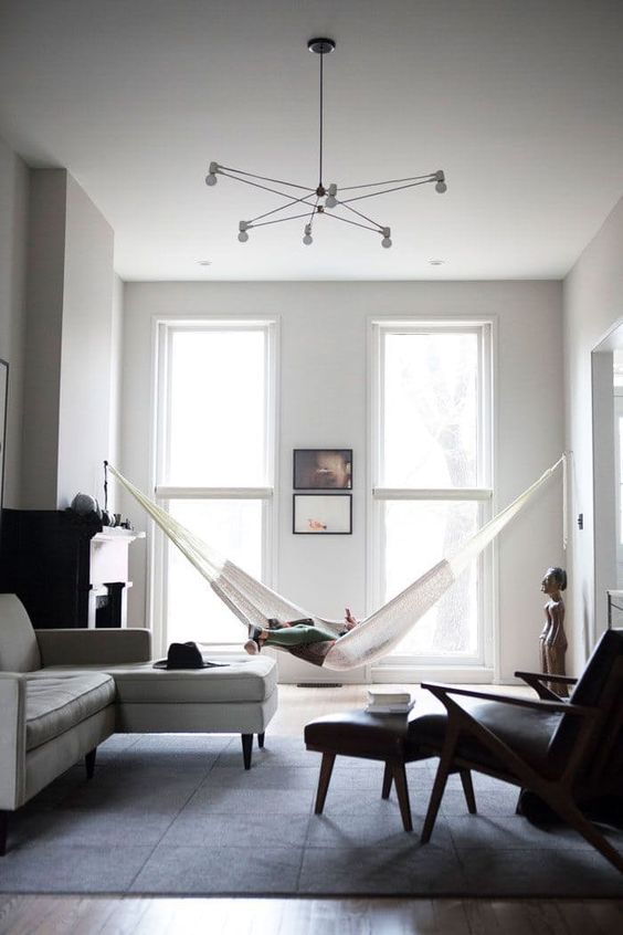 a minimalist black and white living room with neutral and black furniture, a hammock, a fireplace and a catchy chandelier