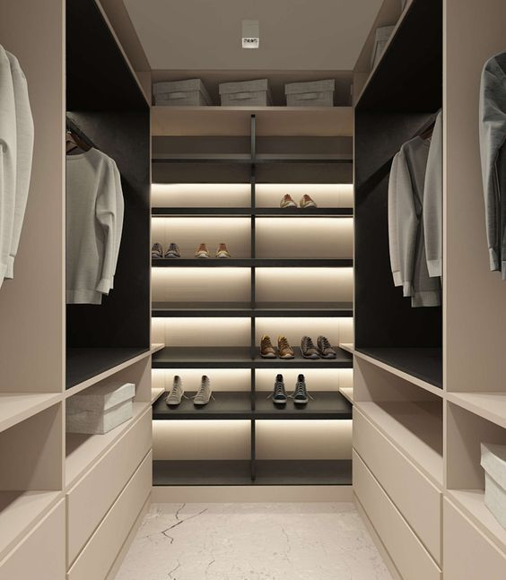 a minimalist closet done in light shades, with black shelves and much built-in light plus drawers