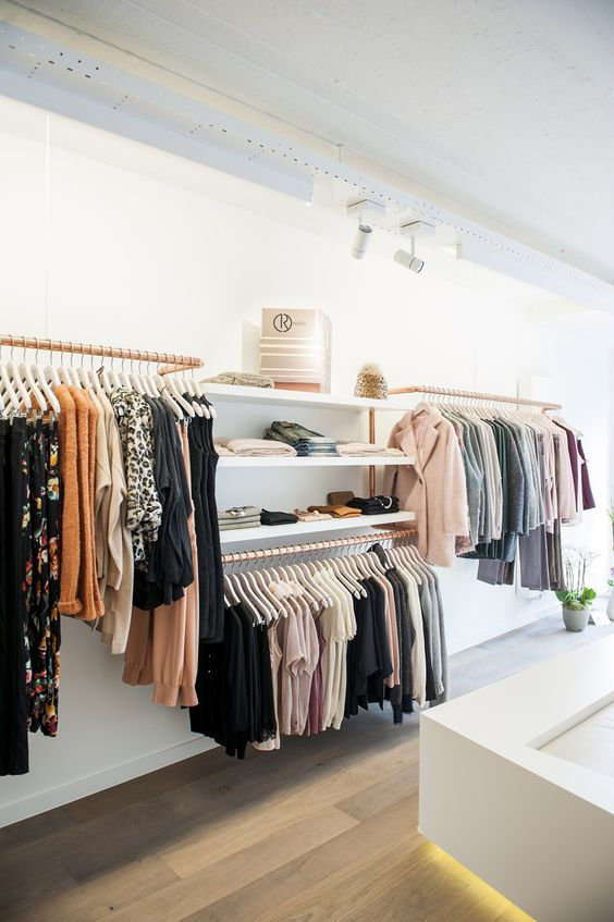 a minimalist closet done of copper holders for hangers and some open shelving is a cool idea to try