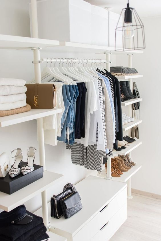 a minimalist closet with lots of open shelves, a dresser and lots of white clothes hangers plus boxes overhead