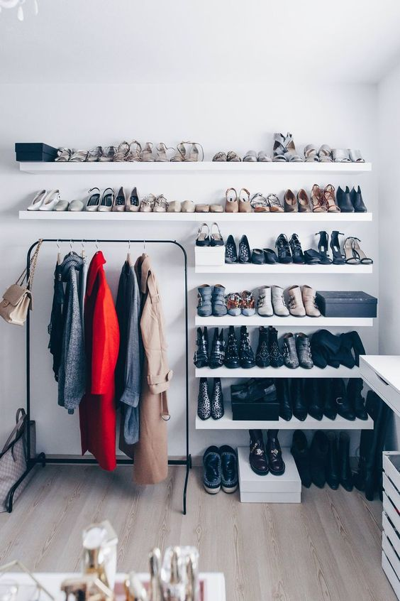 a minimalist closet with lots of open shelves for shoes, a dresser and a black holder for clothes hangers