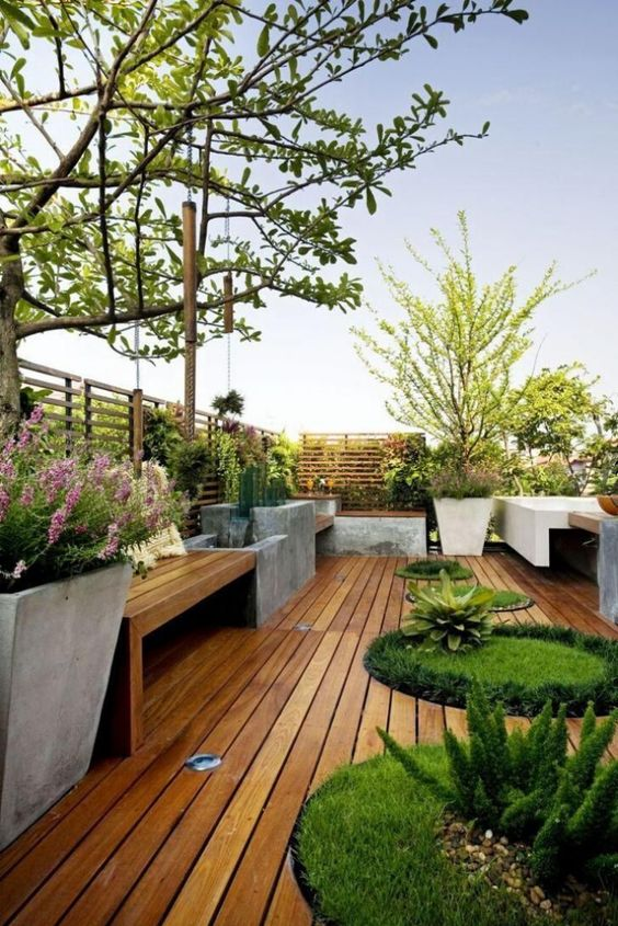 a minimalist deck with built-in benches and concrete planters, round built-in flower boxes with greenery and trees and blooms is like a super-modern garden