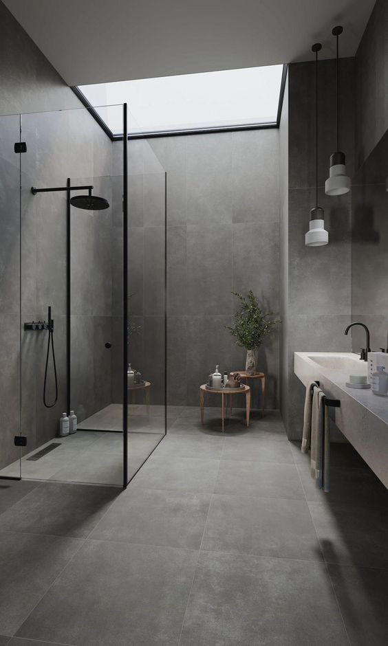 a minimalist grey stone-like tiles, a shower space clad with glass, a floating vanity with a sink and pendant lamps plus a skylight